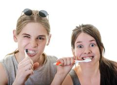 young couple grimacing while brushing their teeth in front of camera - stock photo