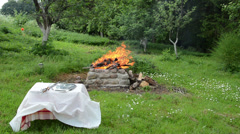 By the fire stands  table covered with white  tight tablecloth Stock Footage