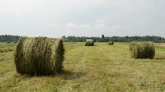 Straw bales agricultural tractor gather hay near village houses Stock Footage