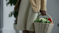 Old woman holds a basket with fresh vegetables Stock Footage