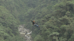 Women ridding a zip line, weaving she's arms like flying, camera pans RL to Stock Footage