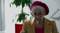 Old woman talking with a window in the back Stock Footage