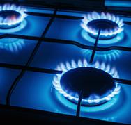 Blue flames of gas burning from a kitchen gas stove Stock Photos