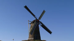 Brick windmill type beltmolen against blue sky Stock Footage