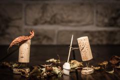 wine cork figures, concept two men clean up foliage - stock photo