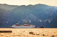 Stock Photo of tourist white cruise sea liner is sailing on the mountain background
