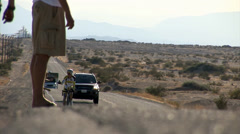 Helpers run along road and hand out bottles of water to their racing collaegues Stock Footage
