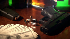 Film noir shot of a gun, bullets, alcohol and 100 dollar bills Stock Footage