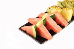 pineapple and watermelon slice arranged in the black dish. - stock photo