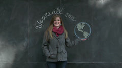 "Cute Girl ""Holds"" the Earth on a ""We Are All One"" Chalkboard Sign Stock Footage"