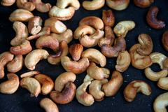 Roasted cashews in the pan. Stock Photos