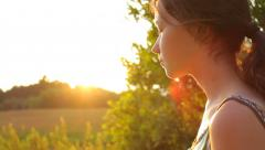 Girl walking in the country in the evening in summer, portrait with sun rays Stock Footage