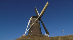 Windmill with turning wicks against blue sky - low angle Stock Footage