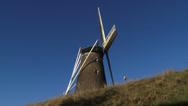 Stock Video Footage of Brick Windmill turning wicks against blue sky - low angle + side view