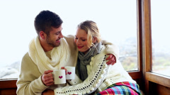 Cute couple cuddling together under a blanket in their ski lodge Stock Footage