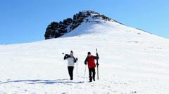 Sporty couple walking down the ski slope Stock Footage