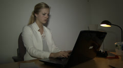 Sad stressed woman behind laptop in the evening - stock footage