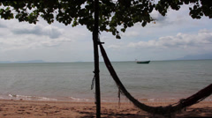 TROPICAL ISLAND: Pan to hammock with small boat on shore of island Stock Footage