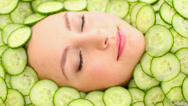 Stock Video Footage of Natural womans face surrounded by cucumber slices