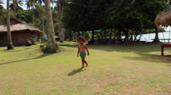 TROPICAL ISLAND: Small Asian child wanders by with huts in background Stock Footage