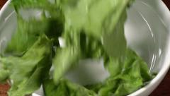 Slow motion shot of lettuce falling into a bowl on a wood table. Stock Footage