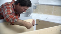 Man putting the bed frame together using the screwdriver Stock Footage