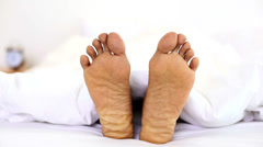Man wiggling his toes under the covers Stock Footage