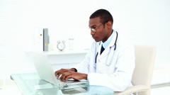 Concentrating doctor working on his laptop - stock footage