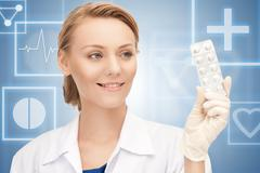 attractive female doctor with pills - stock photo