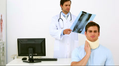 Doctor showing xray to injured patient in neck brace Stock Footage