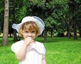 Stock Photo of beautiful little girl in white dress and hat spring season