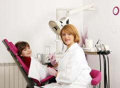 Dentist and little girl in dentist office Stock Photos