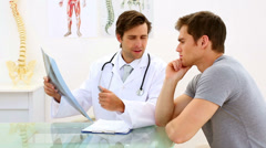 Earnest doctor discussing xray with his patient - stock footage