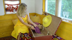 Girl with yellow dress put clothes straw hat on old suitcase Stock Footage