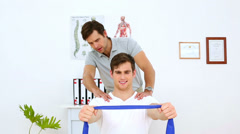 Physiotherapist checking shoulder alignment of patient pulling resistance band Stock Footage
