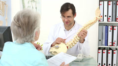 Chiropractor showing spine model to his patient Stock Footage