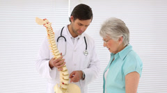 Chiropractor explaining spine model to retired patient Stock Footage