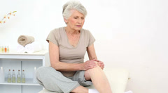 Injured patient rubbing her painful knee - stock footage