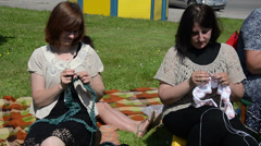 Knitters circle members kniting on field in the summer sun Stock Footage
