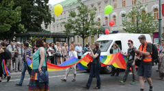 Gay parade walks down street with balloon posters flags Stock Footage