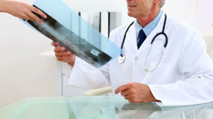 Mature doctor studying at xray at his desk Stock Footage