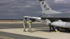 Ground crew check weapons on an F-16 Fighting Falcon jet fighter Stock Footage