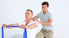 Physiotherapist checking senior patient stretching blue resistance band Stock Footage