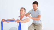 Stock Video Footage of Physiotherapist checking senior patient stretching blue resistance band
