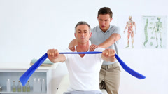 Physiotherapist checking mature patient stretching resistance band Stock Footage