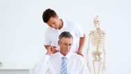 Stock Video Footage of Physiotherapist giving businessman a shoulder rub