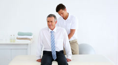 Stressed businessman getting his back checked by physiotherapist Stock Footage