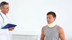 Sportsman in neck brace talking to doctor Stock Footage