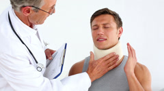 Doctor checking sportsman in neck brace Stock Footage