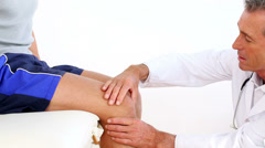 Mature doctor touching sportsmans injured knee Stock Footage